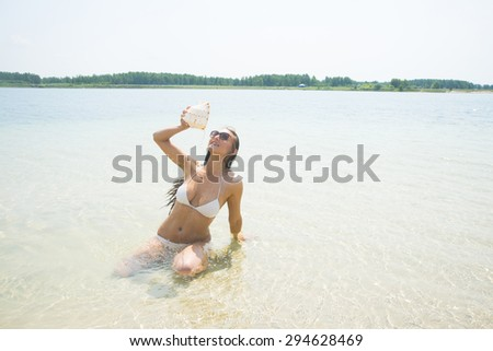 Beach holiday. A smiling brunette hair woman staying at water and pours water from a large conch shell onto herself chest Happy sexy young woman pouring liquid from the big seashell against blue sky