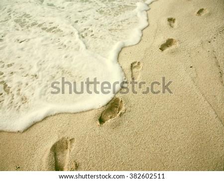 Beach holiday concept. Footprints on beach. Vintage photo - stock photo