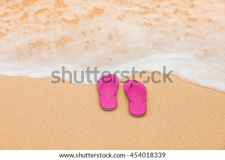 Beach holiday concept. Pair of sandals on the beach.  - stock photo