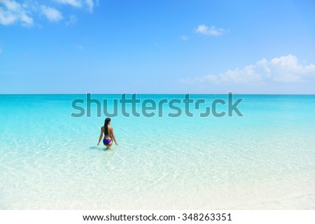 Beach holiday person swimming in blue ocean. Sexy bikini woman relaxing enjoying her tropical vacation in the Caribbean in a paradise destination with perfect turquoise water and white sand. - stock photo