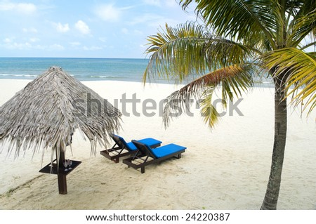 Beach holiday - Tropical beach with hut and chairs - stock photo