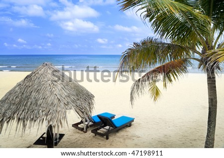 Beach holiday. Tropical beach with hut and chairs. - stock photo