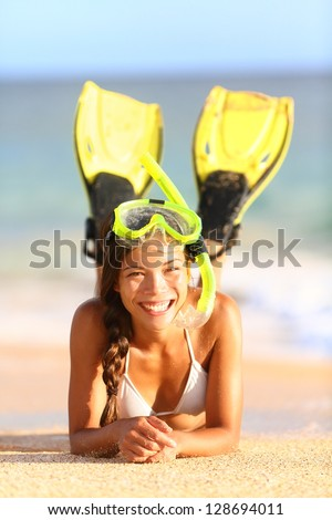 Beach holiday vacation woman snorkeling fun. Joyful happy woman wearing snorkeling equipment, fins and mask, lying down in water and sand looking at camera. Beautiful mixed race Caucasian Asian model - stock photo