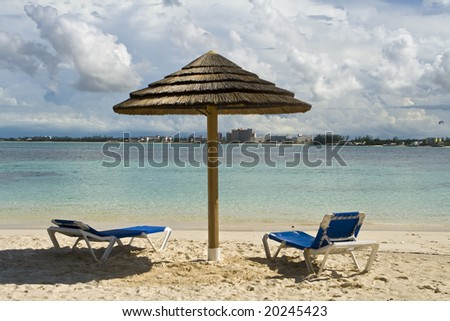 Beach hut and chairs on tropical shoreline of a resort. - stock photo