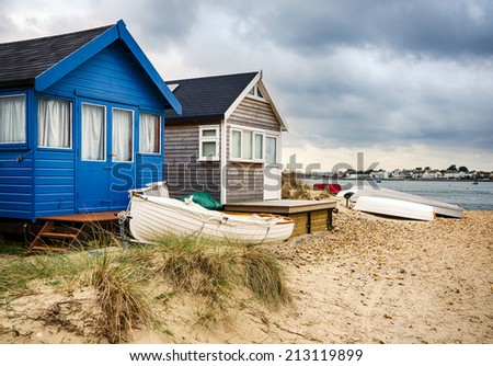 Beach huts and boats in sand dunes at Mudeford Spit on Hengistbury Head near Christchurch in Dorset - stock photo