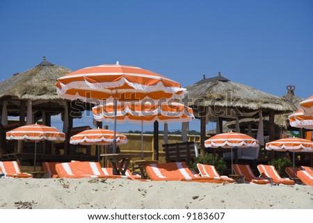 beach huts and umbrellas - saint-tropez, french riviera - stock photo