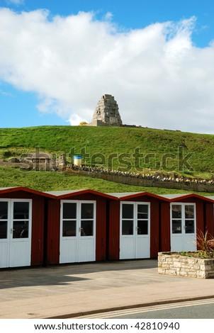 Beach huts and war memorial in Swanage, Dorset (UK) - stock photo