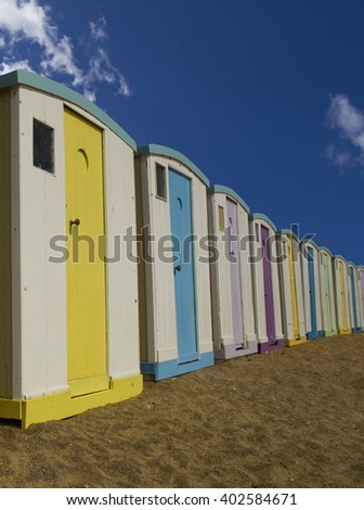 Beach huts lined up with a blue sky in summer on the beach  - stock photo