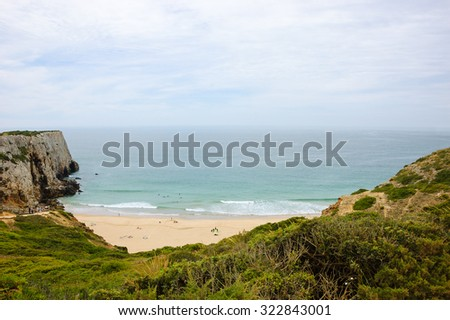 Beach in Algarve region of Portugal in cloudy day. People swimming and surfing. A view from the top. - stock photo
