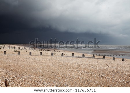 Beach in bad weather, coast with dark storm clouds. Winchelsea in england sussex with view of groyne wood pillars - stock photo