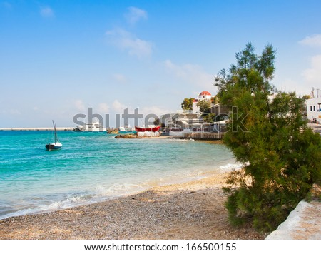Beach in Mykonos Chora and the famous Tavern on the sea with a red boat and the church - stock photo