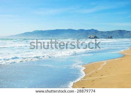 Beach in San Francisco California with waves coming to the sand and blue sky background. - stock photo