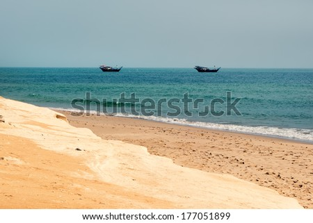 Beach in South Oman, with typical fishing boats in background and last piece of desert in foreground