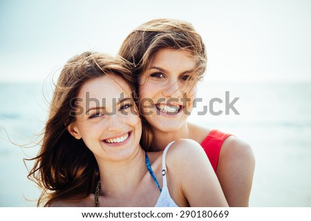 Beach in summer. A couple of young women in swimwear hugging affectionately in the sun on a summer day. Close-up photo of the smiling faces - stock photo