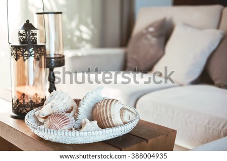 Beach interior decor: sea shells and lanterns on the wooden coffee table, natural colors. Detail of living room. - stock photo