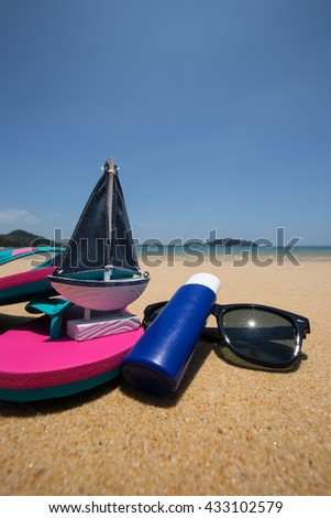 Beach items - body lotion, pink flip flops and Sunglasses. - stock photo