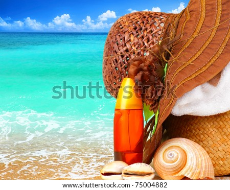 Beach items over blue sea conceptual image of summertime vacation & holidays - stock photo