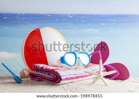 Beach items with flip flops,sunblock,beach ball and sunglasses - stock photo