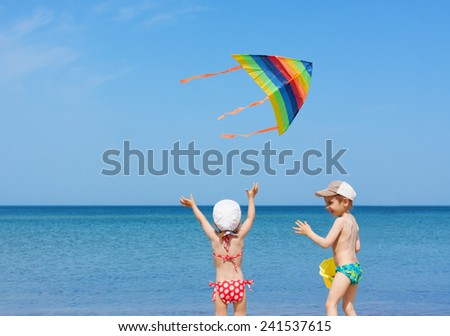 beach  kite fly children siblings play fun together - stock photo