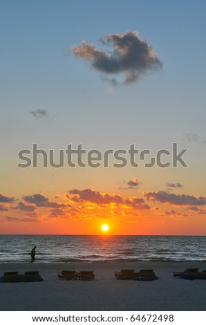 Beach Landscape moments before sunset with folded up beach chairs in the foreground. St. Pete, Florida - stock photo