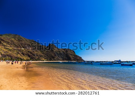 Beach Las Teresitas with water and waves on yellow sand on coast or shore of Atlantic ocean on Tenerife Canary island, Spain. Blue sky and mountain at the background - stock photo