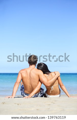 Beach lifestyle couple in love on vacation. Happy young interracial couple embracing and hugging enjoying ocean sea view and summer sun and blue sky during holidays travel. Asian woman, Caucasian man. - stock photo