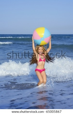 Beach little girl colorful ball vacation playing in blue sea - stock photo
