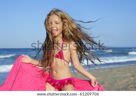 Beach little girl playing pink towel and wind in blue sea - stock photo