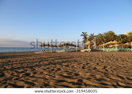 Beach lounge chair and beach umbrella at lonely sandy beach. Costa del Sol (Coast of the Sun), Malaga in Andalusia, Spain