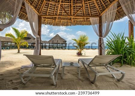 Beach lounge chairs and a beach bar at the shore of Indian ocean, Zanzibar, Tanzania - stock photo