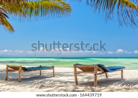 Beach Lounge chairs under palm tree leaves at the shore of Indian ocean, Zanzibar, Tanzania - stock photo