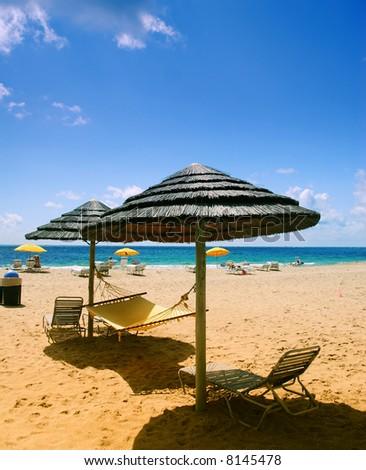 Beach lounge chairs under shade of umbrellas - stock photo