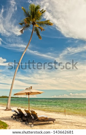 Beach Lounge Chairs with towels under umbrella under palm tree at the shore of Indian ocean, Zanzibar, Tanzania - stock photo