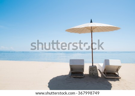 Beach lounge chairs with umbrella on the beach - stock photo
