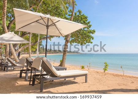 Beach loungers and parasol at the beach of Bali island, Indonesia - stock photo