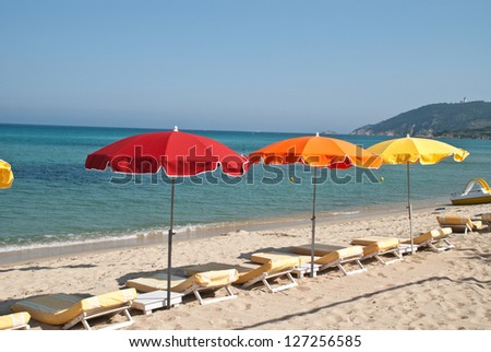 Beach loungers and parasol on the beach of St. Tropez, France. - stock photo
