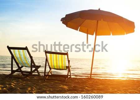 Beach loungers on deserted coast sea at sunrise, Thailand. - stock photo