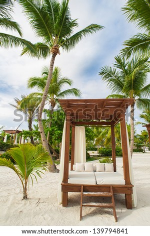 beach loungers, Palm and tropical beach in Tropical Paradise. Summertime holyday in Dominican Republic, Seychelles, Caribbean, Philippines, Bahamas.  Paradise beach. Luxury Resort on Atlantic ocean. - stock photo