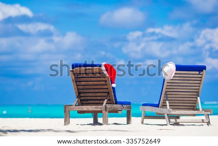 Beach loungers with red Santa and straw hat background beautiful turquoise sea  - stock photo