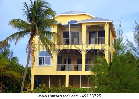 Beach mansion with palm trees - stock photo