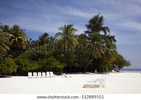 Beach of an idyllic vacation island in the Maldives with lush palm trees and beach beds. - stock photo
