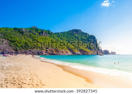 Beach of Cleopatra with sea and rocks of Alanya peninsula, Antalya, Turkey. Beautiful landscape of tourist destination with high green cliff and Castle of Alanya. - stock photo
