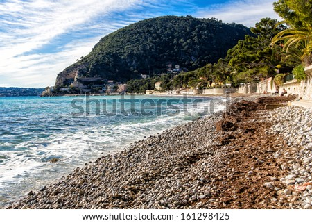 Beach of Eze sur mer in south of france with mountain in the background - stock photo
