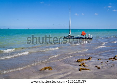 Beach of Maceio in Alagoas, Brazil. Shows a jangada, a small boat made by hand, and the beauty blue sky and sea during summer. - stock photo