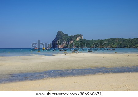 Beach of Phi Phi island in low tide with bay and longboat on background, Krabi province, Thailand - stock photo