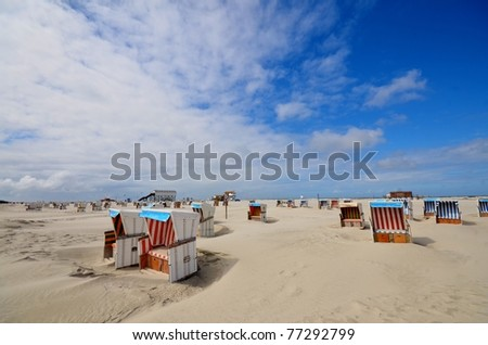 beach of St. Peter Ording at the german Atlantic coast with hooded beach chairs - stock photo