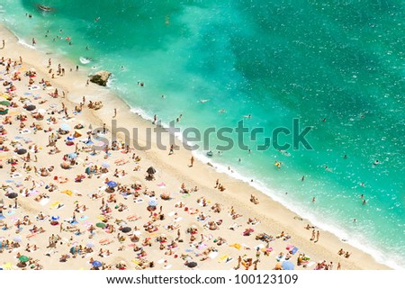 beach of the Cote d'Azur with tourists, sunbeds and umbrellas on the hot summer day. french riviera, Provence, France - stock photo