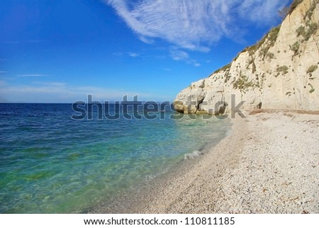 Beach of white pebbles under a high white cliff, in front of a beautiful water (Capo Bianco, Elba Island, Italy) - stock photo
