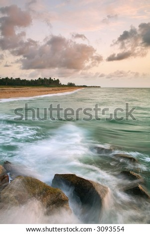 beach on atlantic ocean with spray against rock jetty at dawn