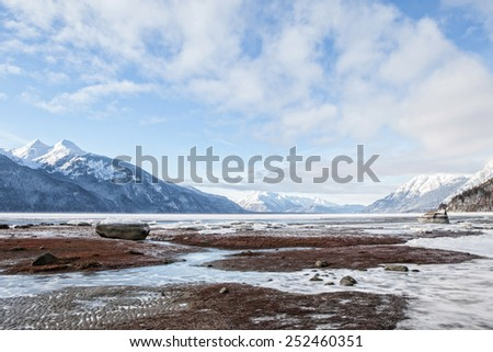 Beach on the Chillkat River near Haines Alaska on a winter day with ice and snow. - stock photo